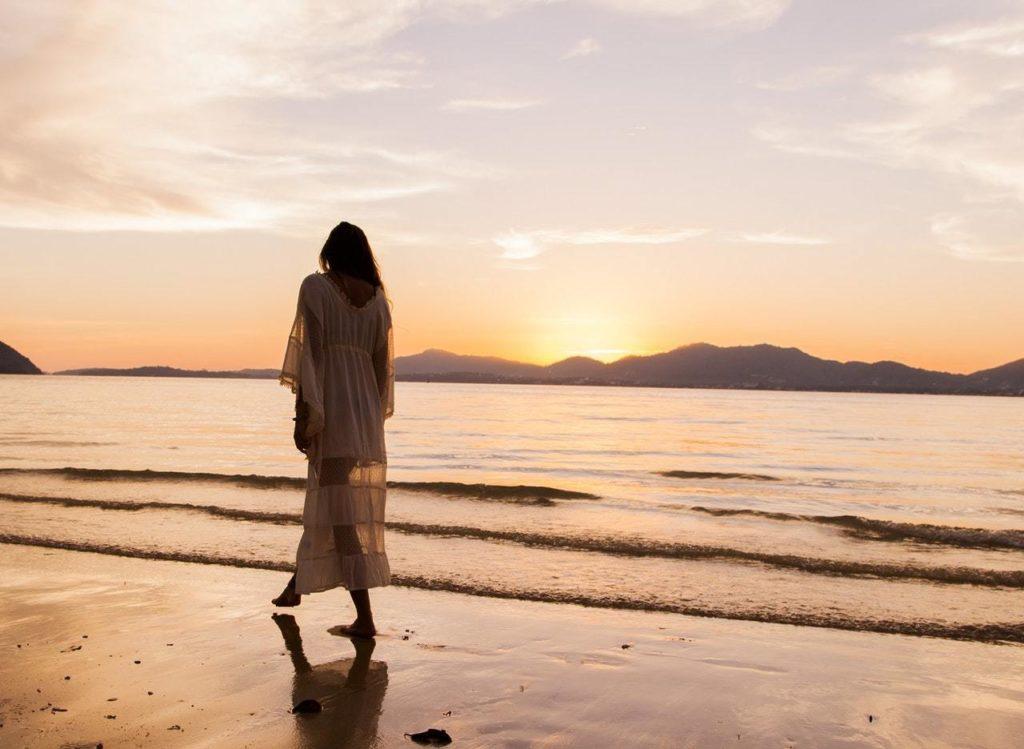 woman walking on beach in evening